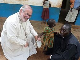 Fr. Joseph with a child in Uganda.